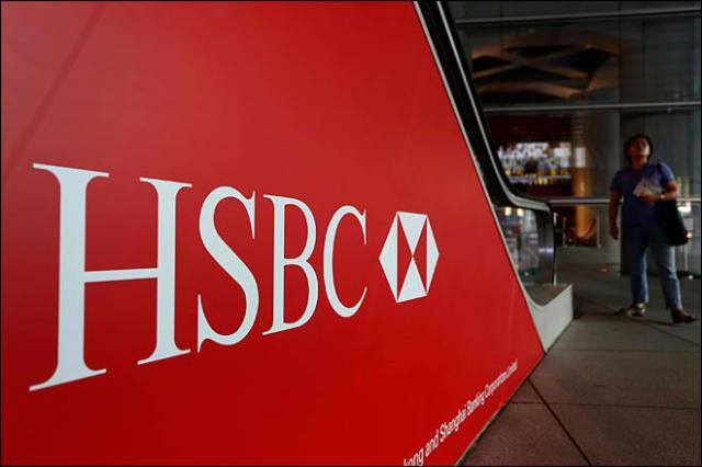 People walk past a logo of HSBC headquarters in Hong Kong Monday, July 30, 2012. (AP Photo/Vincent Yu)